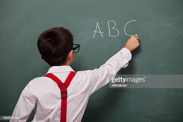 Backview of little boy writing alphabet on green blackboard