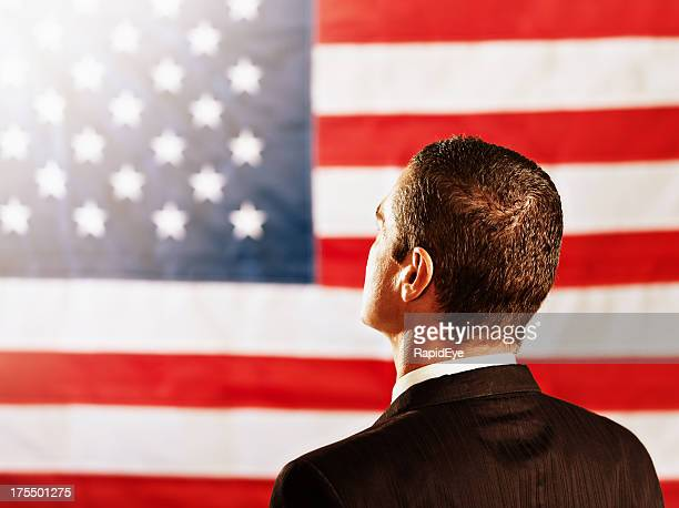Backview of politician or businessman looking at US national flag