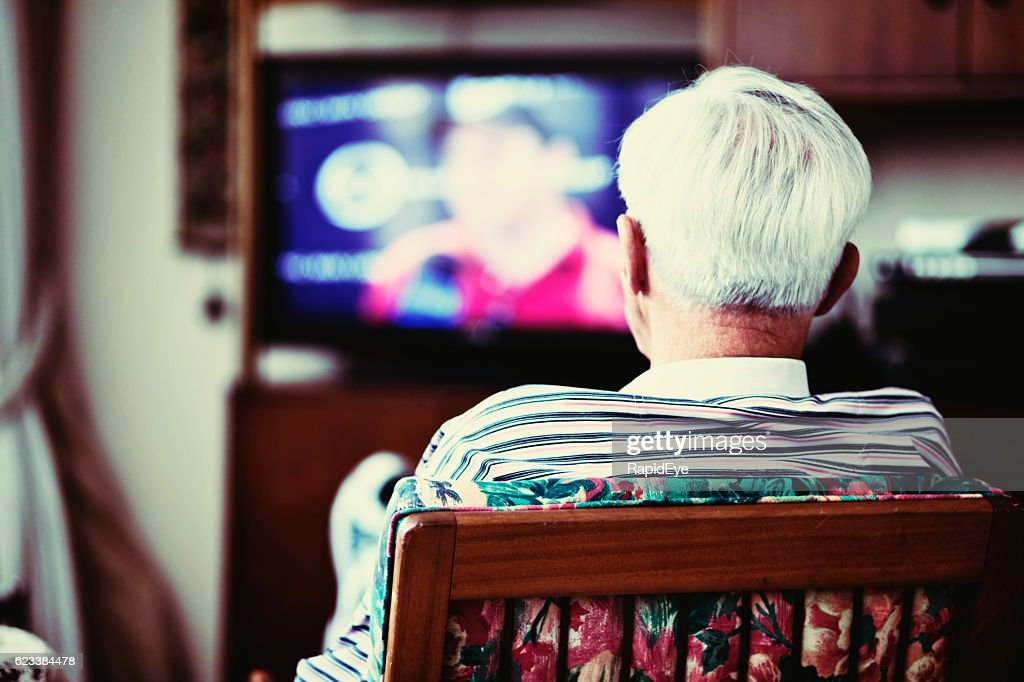 Backview of solitary very old man watching TV : Stock Photo
