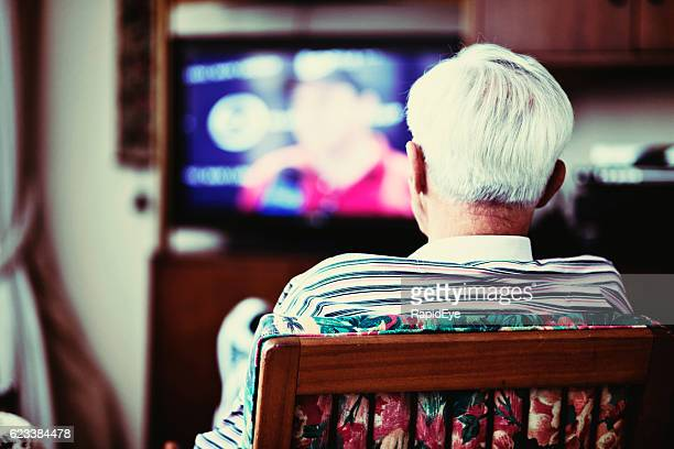 backview of solitary very old man watching tv - television industry stock photos and pictures