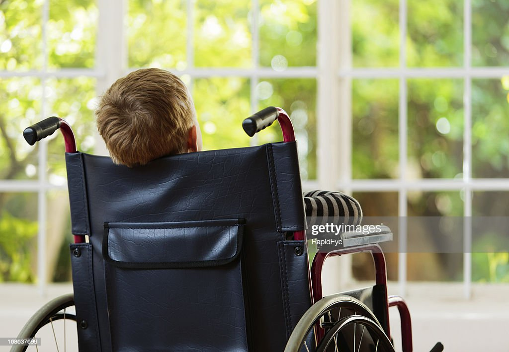 Backview of wheelchair-bound boy watching garden he cannot play in : Stock Photo