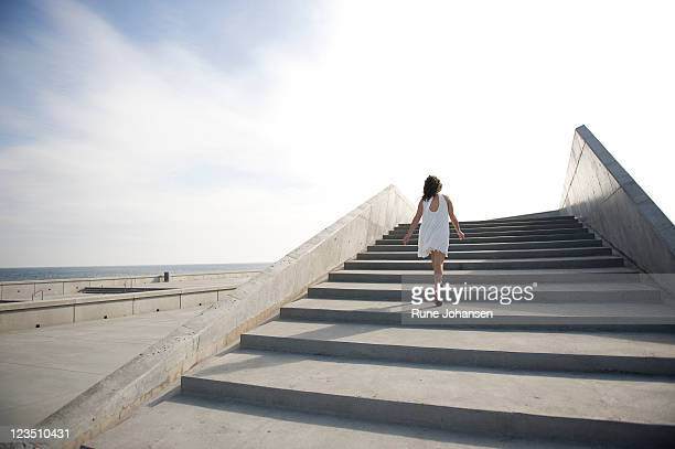 Backview of young Danish woman, 26 years old, outdoors walking up steps at Amager Strandpark, Copenhagen, Denmark