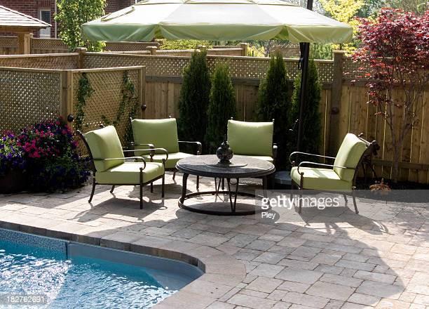 Backyard furniture next to an inground pool