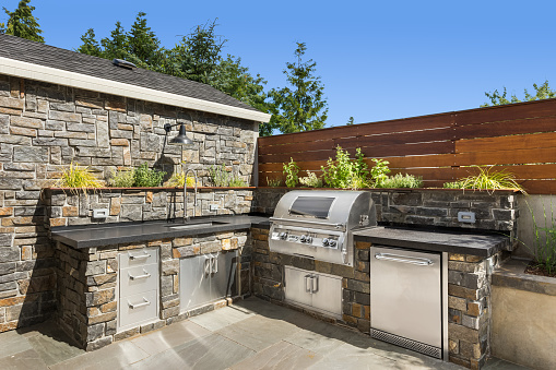 Backyard hardscape patio with outdoor barbecue and kitchen 1211179492