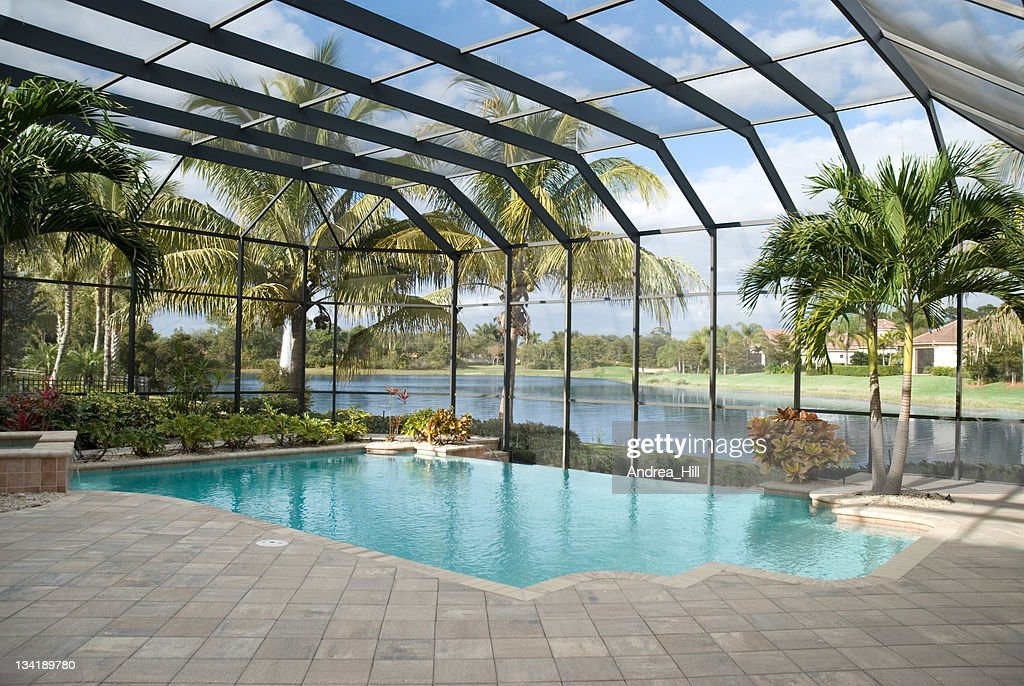 Backyard pool with window panel and ceiling next to lake : Stock Photo