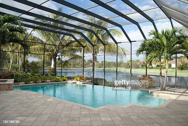 Backyard pool with window panel and ceiling next to lake