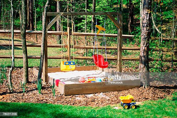 Backyard with a child's sandbox and toys.