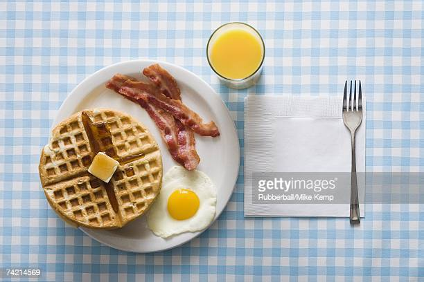 Bacon and eggs with waffle and orange juice with napkin and fork