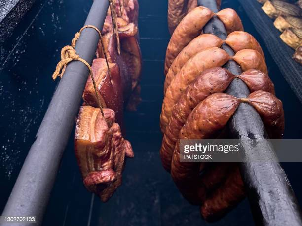 bacon and sausages hanging on rack in a smokehouse. - gerookte worst stockfoto's en -beelden