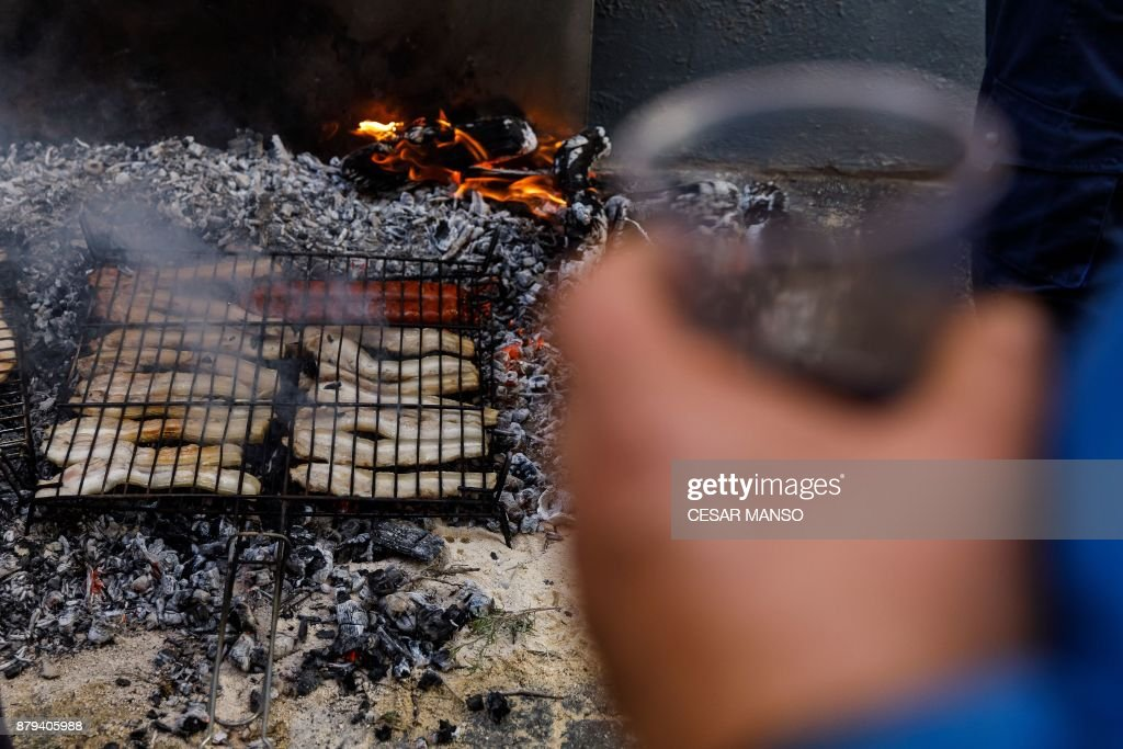 Bacon grills on a bonfire after the 'Procession of smoke' in the northern Spanish village of Arnedillo on November 26, 2017. Locals light bonfires with rosemary and juniper to produce smoke that covers Arnedillo streets while the patron saint San Andres is paraded in procession. /