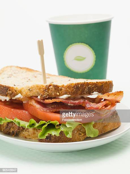 Bacon, lettuce and tomato sandwich with drink in background, close up