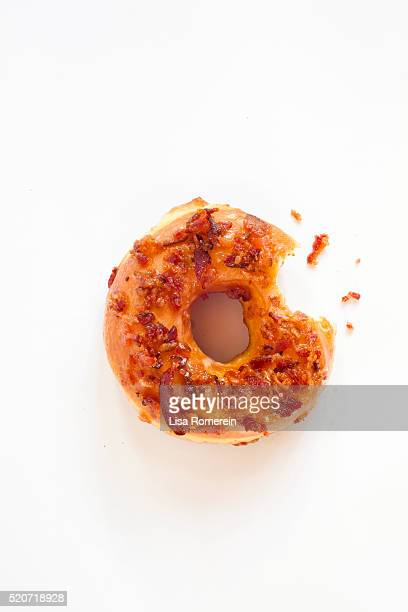 Bacon maple donut with bite on white