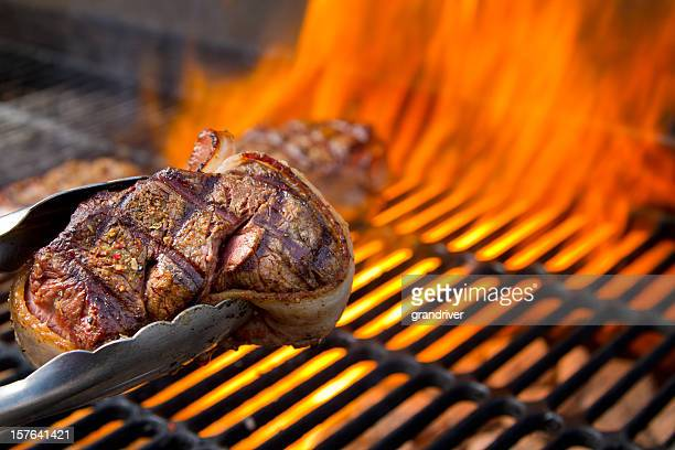 bacon wrapped beef filet mignon on grill with dancing flames - seared stock photos and pictures