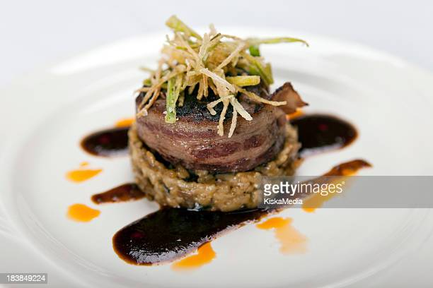 Bacon wrapped filet mignon with garnish on white plate