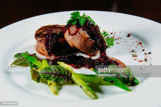 Bacon wrapped pork medallions with caramelized onion and asparagus
