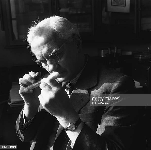 Bacteriologist Sir Alexander Fleming examines the contents of a test tube in his laboratory at the WrightFleming Institute