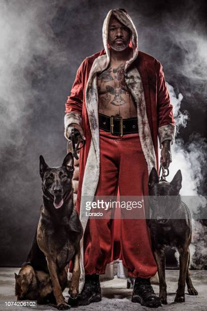 bad black santa claus with dogs - dirty santa stock pictures, royalty-free photos & images