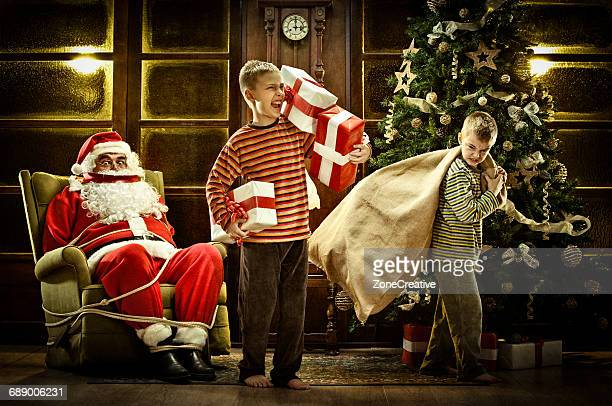 bad children steal santa claus gift - bad santa stock-fotos und bilder