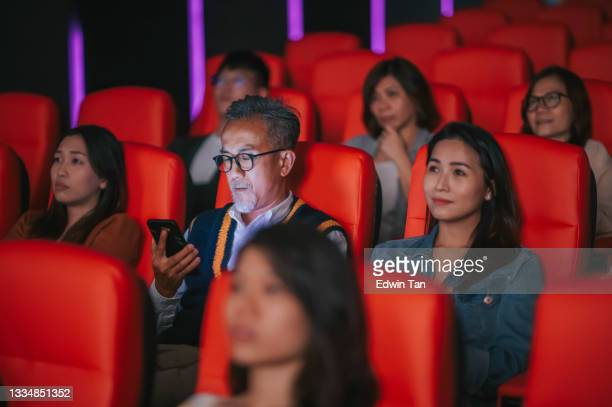 bad habit rude asian chinese senior man reading smart phone text message during cinema movie show time in the dark disturbing and ignoring other audience around him - film premiere stock pictures, royalty-free photos & images