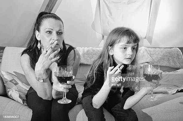 bad role model mother with daughter - little girl smoking cigarette stock photos and pictures