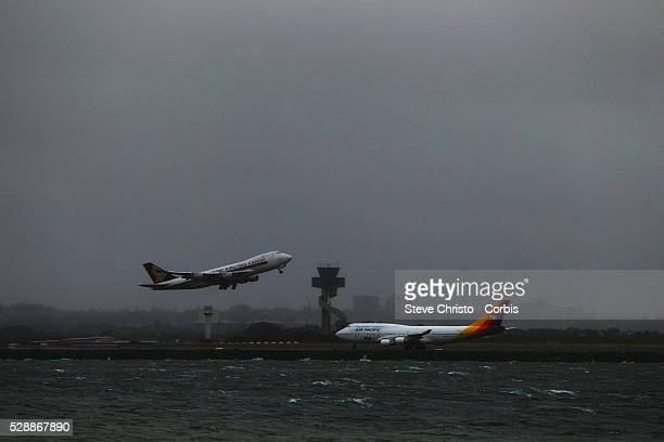 Bad weather and Coastal winds around Sydney Airport as a Singapore Airlines cargo plane takes off in front of an Air Pacific plane on the third...