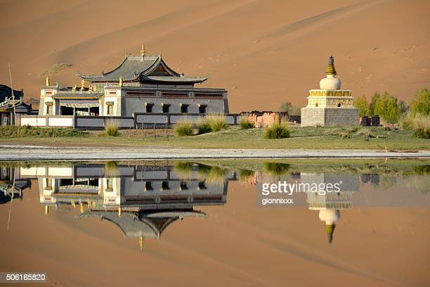 Badain Jaran Temple, reflecting on its lake, Inner Mongolia
