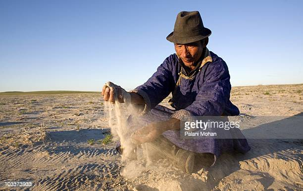 Badamusileng a Mongolian nomadic herder runs sand from a dry lake bed through his hands on August 22 west of Mandubaolage Local people have watched...