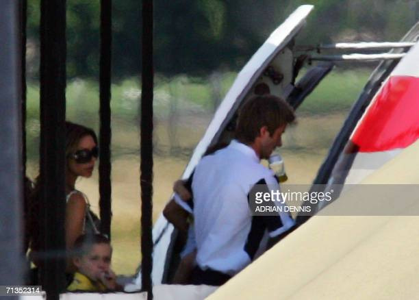 English midfielder David Beckham with a baby bottle in his mouth boards a British Airways jet followed by his wife Victoria and son Brooklyn at Baden...