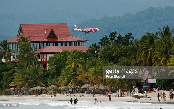 Badende Einheimische und Touristen am Strand dahinter Air AsiaFlugzeug Insel Langkawi Malaysia Meer Badende Flieger landen Airline Reise NB DIG PNr...