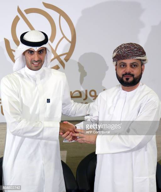 Bader AlKharafi vicechairman and Group CEO of Zain Group shakes hands with Omantel CEO Talal Said AlMamari during a press conference at the Boursa...