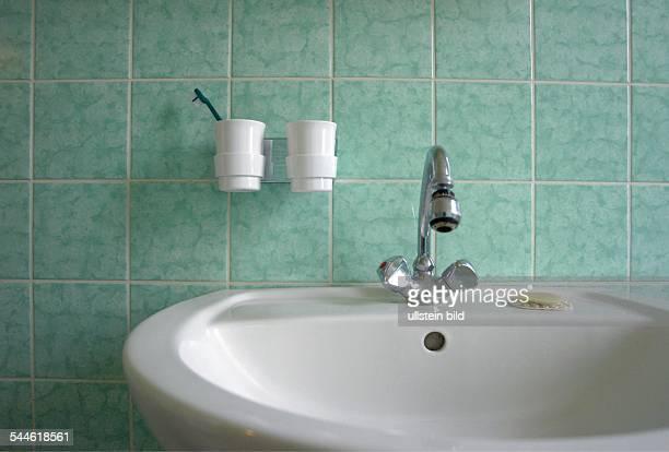 Badezimmer mit grünen Kacheln Waschbecken mit Wasserhahn einem Stück Seife und zwei weissen Zahnputzbechern