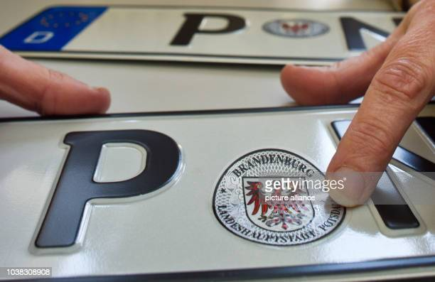 A badge of the state of Brandenburg is attached to a new licence plate at the vehicle registration office in Potsdam Germany 22 April 2013 The...