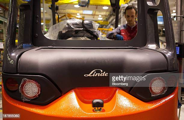 A badge sits on a Linde E25 electric forklift truck as an employee works on the vehicle at the Linde Material Handling GmbH factory a unit of Kion...
