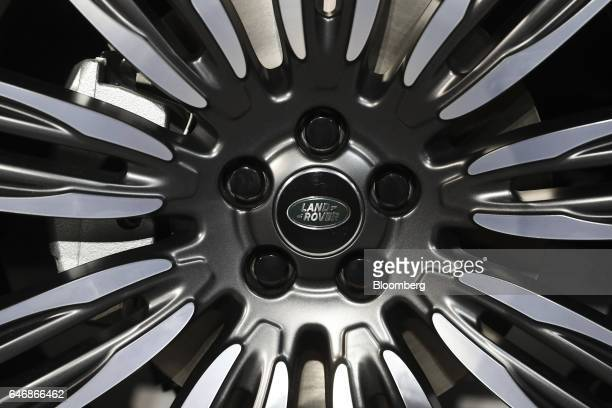 A badge sits on the alloy wheels of a Range Rover Velar sports utility vehicle manufactured by Jaguar Land Rover Automotive Plc as it stands during a...