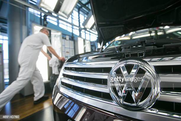 A VW badge sits on the front grill of a Volkswagen Phaeton automobile during quality control checks at the Volkswagen AG factory in Dresden Germany...