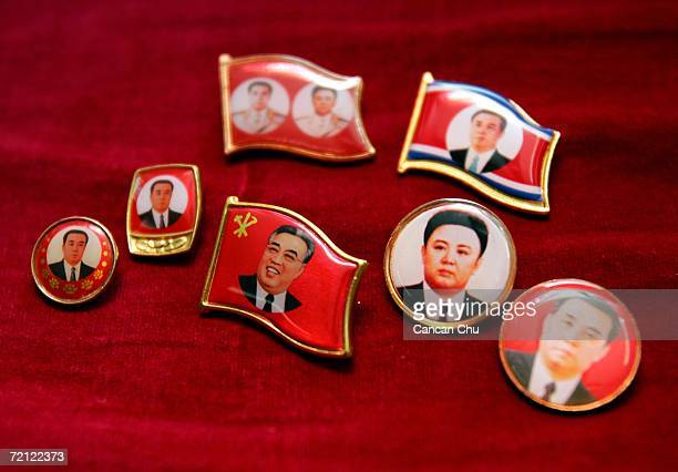 Badges featuring North Korean leader Kim JongIl and his late father Kim IlSung are sold at a souvenir shop October 9 2006 at the border city of...