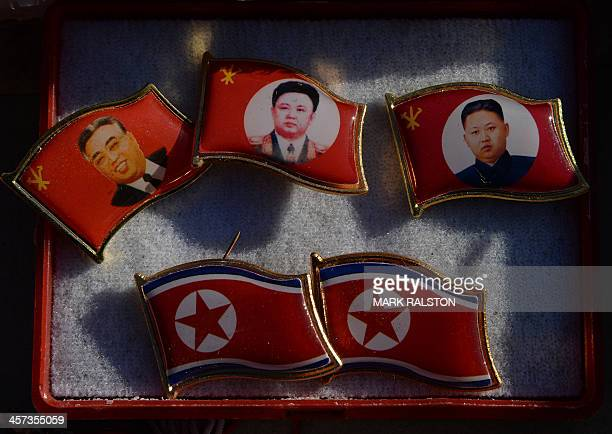 Badges showing late North Korean leaders Kim Il Sung and Kim Jong Il and new leader Kim JongUn for sale by a street vendor in the Chinese border town...