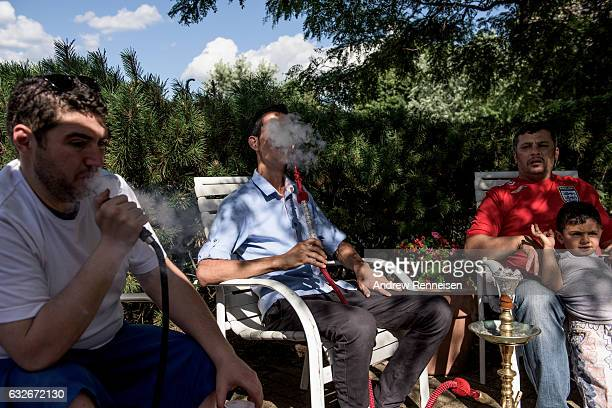 Badi Dabjan a volunteer in the Syrian community and asylum seeker smokes hookah with Nedal Al Hayek and Thaer Hoshan both refugees from Daraa Syria...
