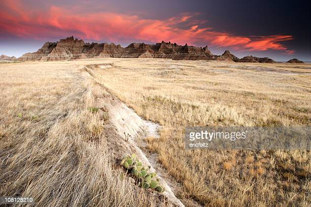 badlands and prairie field at sunset - great plains stock pictures, royalty-free photos & images