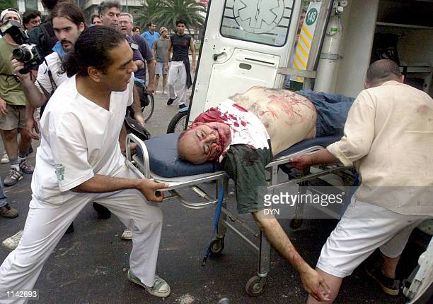 A badly injured man is placed into an ambulance by paramedics during an antigovernment protest December 20 2001 in Buenos Aires Argentina Anger over...