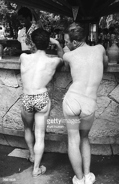 A badly sunburned holidaymaker admires his friend's leopardprint briefs while standing at the bar of a holiday camp on Corfu Original Publication...