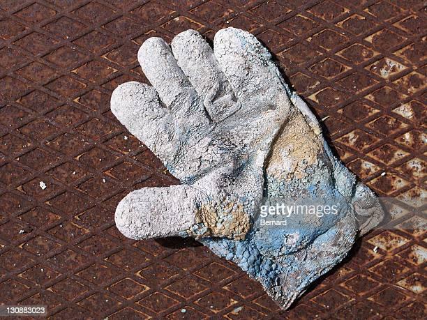 Badly worn work glove on rusty metal plate