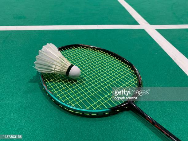 badminton balls placed on badminton rackets in the field - badminton sport stock pictures, royalty-free photos & images