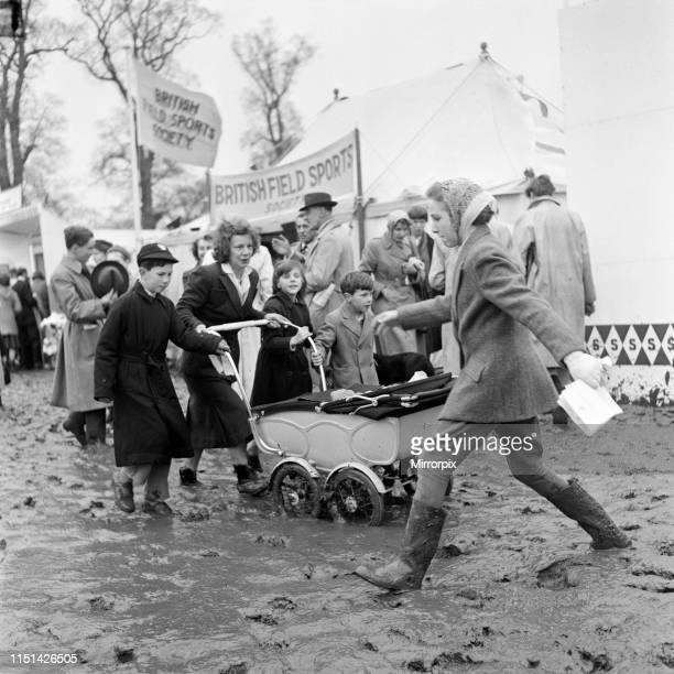 Badminton Horse Trials, Badminton, Gloucestershire. A woman pushing a pram through a muddy field. 17th April 1959.