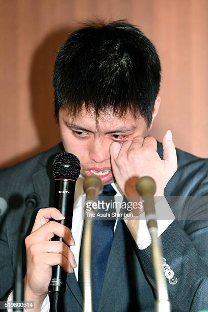 Badminton players Kenichi Tago sheds tears while speaking during a press conference on April 8 2016 in Tokyo Japan Both players admitted to have gone...