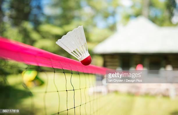 Badminton shuttle cock flying over badminton net