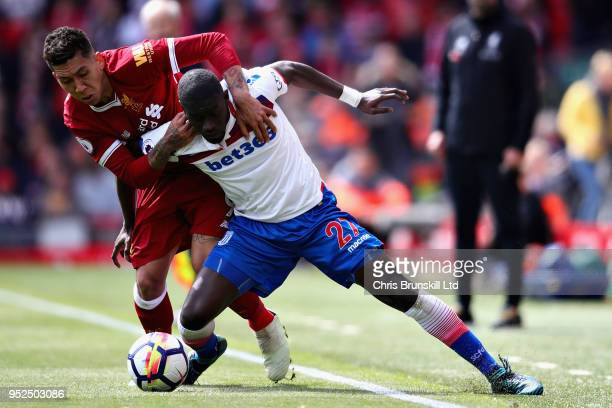 Badou Ndiaye of Stoke City is challenged by Roberto Firmino of Liverpool during the Premier League match between Liverpool and Stoke City at Anfield...