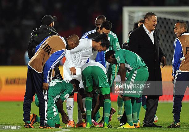 Badr Kachani and Vivien Mabide of Raja Casablanca take Ronaldinho of Atletico Mineiro's boots at fulltime following the FIFA Club World Cup Semi...