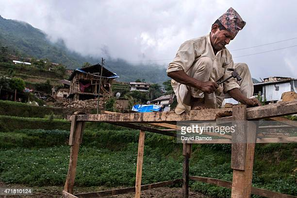 Badri Prasad Chaulagain works to build a makeshift shelter next to his collapsed home on May 1 2015 in Bhotechaur Nepal A major 78 earthquake hit...