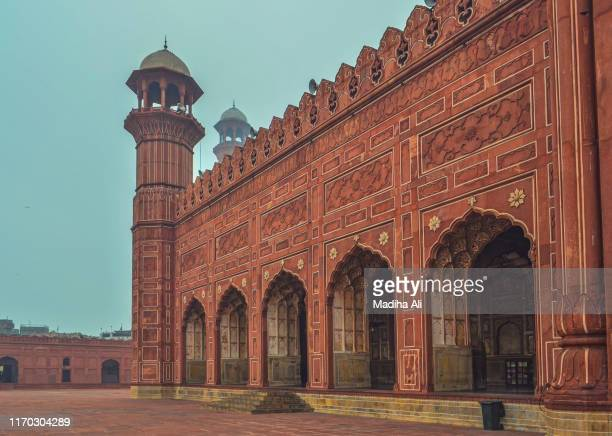 badshahi jama mosque / masjid in lahore, pakistan is an architectural marvel made from red bricks, with arch, dome and minarets and used for prayer hall in friday, ramadan kareem, eid-ul-fitr, eid-al-adha and muharram - pakistan stock-fotos und bilder